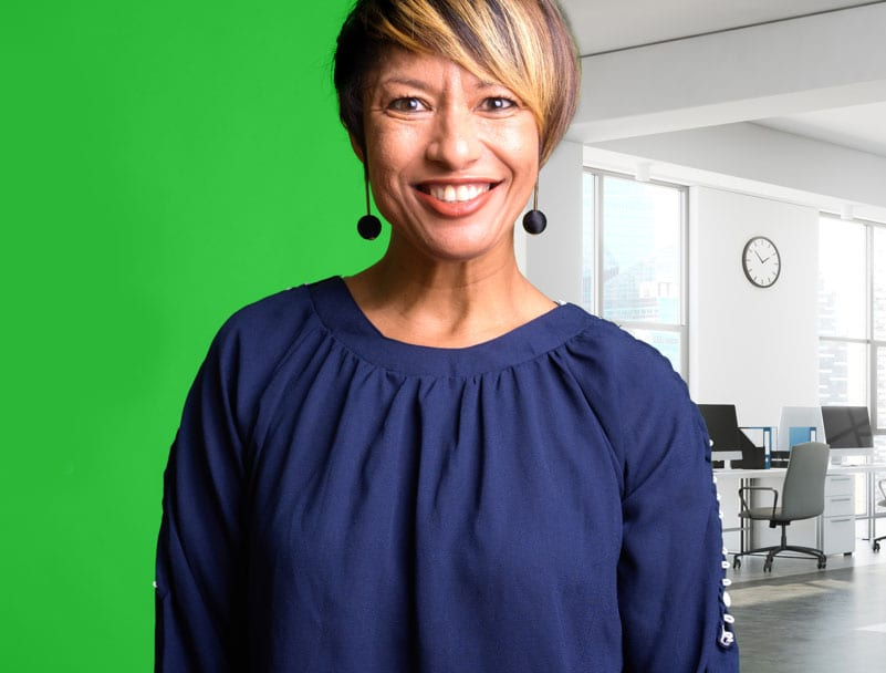 Woman standing in front of a green screen. Green screen on left side and a virtual office on the right side.
